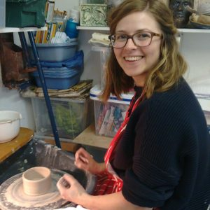 student creating a pot on a potters wheel with Northern Irish artist McCall Gilfillan